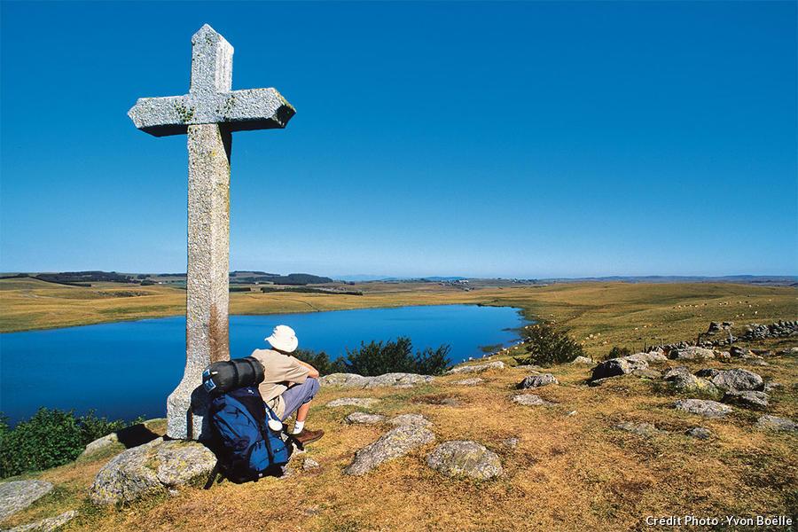 Un pélerin assis sous une croix